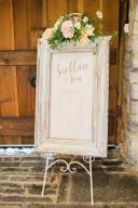 romantic table plan for wedding guests in a large frame adorned with flowers