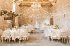 almonry barn wedding set up with round tables and a canaopy of twinkling lights above