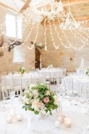 white table linens with pink floral centrepieces by Amber Persia