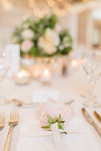 blush pink rose places at the place setting at the wedding