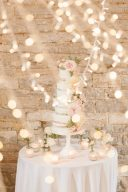 beautiful wedding cake seen through the fairylights