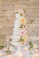 four tier wedding cake dressed with real flowers