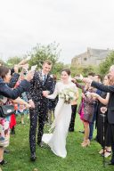 bride and groom showered with confetti at almonry barn