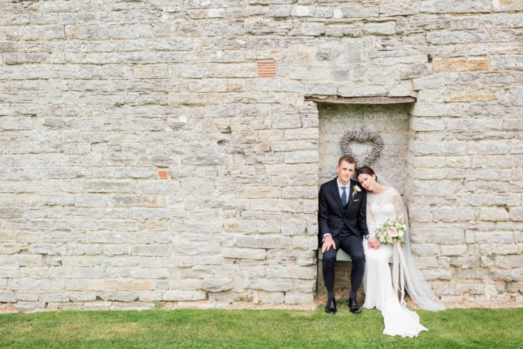 sweet bride and groom portrait with a background of cream bricks of almonry barn