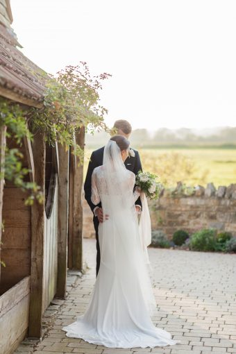 bride and groom photograph posing by the barn wedding venue