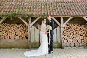 bride and groom pose by the piles of cut wood at almonry barn