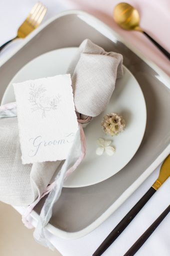 creative wedding place setting with grey plates lenen napkins and calligraphy stationery
