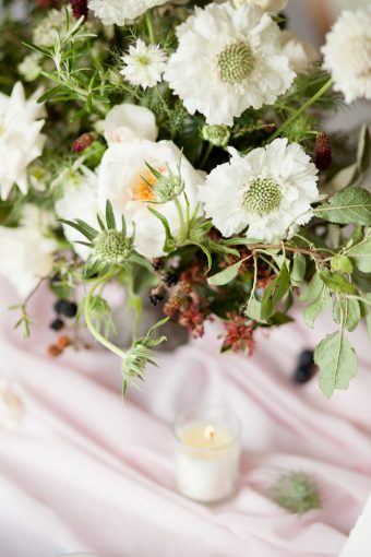 whimsical wedding flowers styled on a pink silk table runner