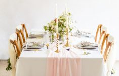 white table etting with blush pink runner and brass candlesticks