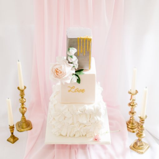 opulent three tier wedding cake design in white and dripping gold