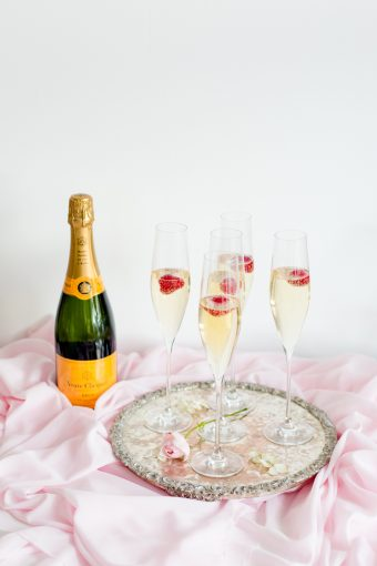 silver tray of champagne styled on a blush pink silk runner