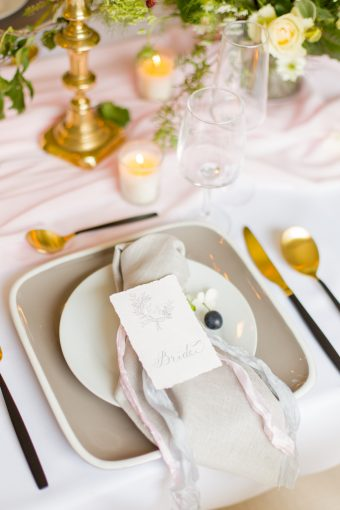 creative wedding place setting with grey plates lenen napkins and calligraphy stationery and modern black and gold cutlery