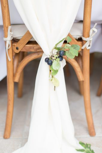 wooden cross back wedding chair decorated with white silk and foliage