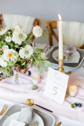 wedding table decor styling with pink silk runners and calligraphy stationery table number