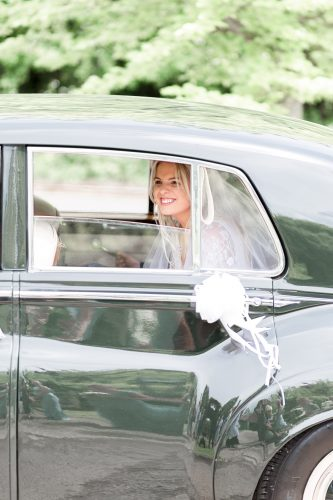 bride arriving at church in timeless black car