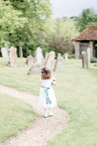 flower girl wearing white with turquoise ribbon sash