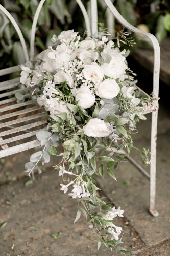 green and white bridal bouquet on a bench