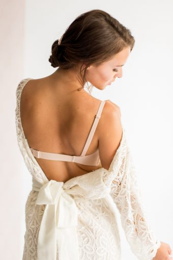 bride getting dressed with lace gown and wonderbra