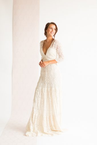 bride wearing a modern lace wedding dress with v neck and three quarter sleeves