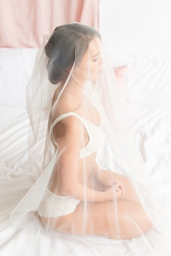 bridal morning portrait of the bride in her wonderbra lingerie with her veil draped over her