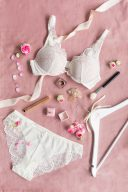 flatlay of wonderbra bridal collection on pink with bridal details such as ring box and roses