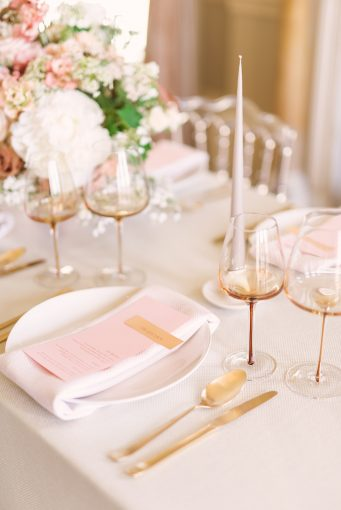pink and gold table setting with amber glassware
