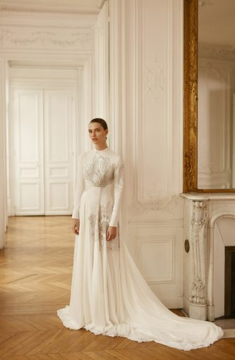 Fashionable wedding dress with long sleeves and sparkly floral embellishments by Dana Harel
