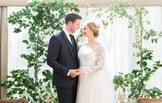 intimate wedding ceremony with floral arch and elegant bridal style