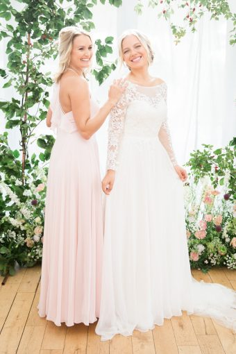 blush bridesmaids dress and bride with lace sleeve wedding dress