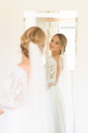 bride wearing v-back wedding dress with lace sleeves by Stelfox Bride