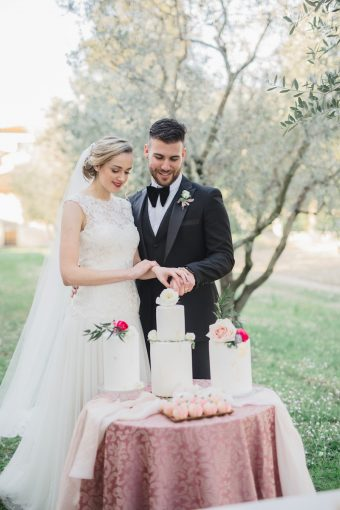 couple cutting a trio of wedding cakes
