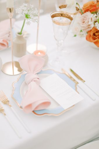 blush and powder blue place setting with gold cutlery