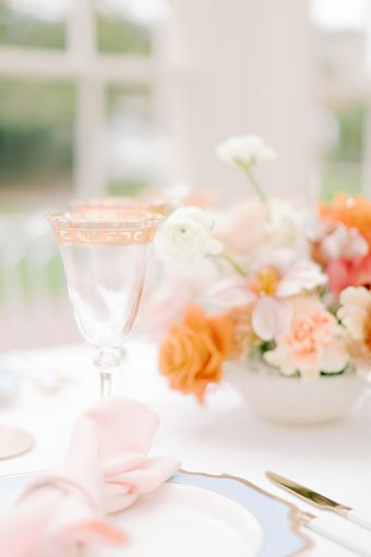 gold rimmed glasses with peach and orange spring floral arrangement