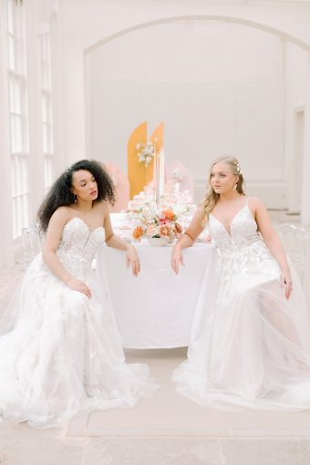 two brides seated at modern pastel spring wedding table