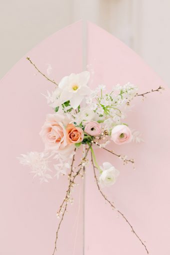 pretty spring wedding florals including narcissi and ranunculus on a pink backdrop