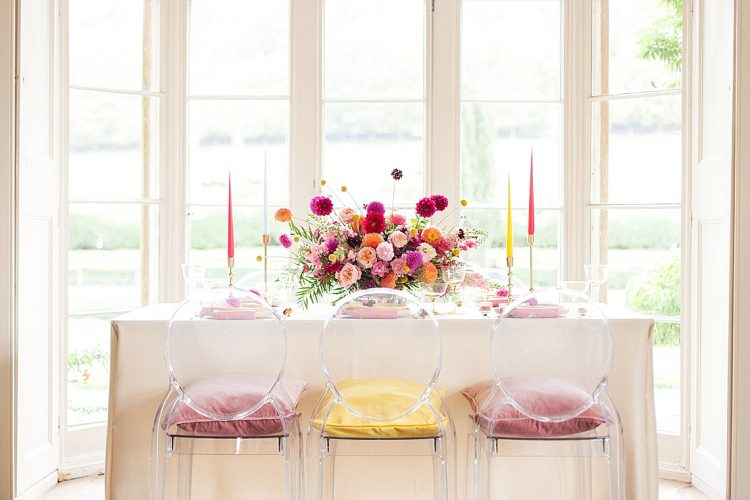beautifully vibrant pink & yellow wedding table with ghost chairs and candles