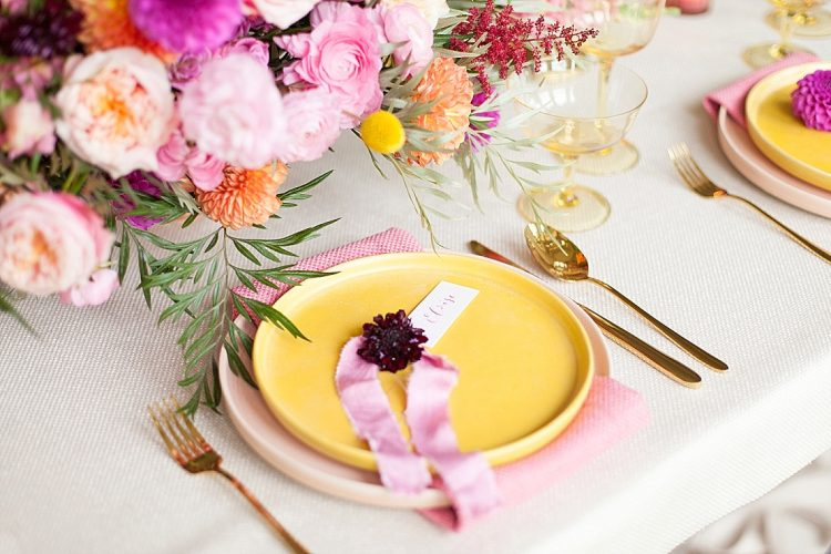 bright pink dahlia and pink silk ribbon with calligraphy place card on yellow place setting
