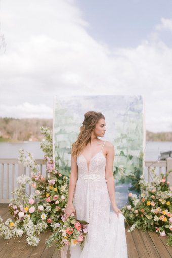 bespoke wedding dress with deep v neckline and painted wedding ceremony backdrop with flowers