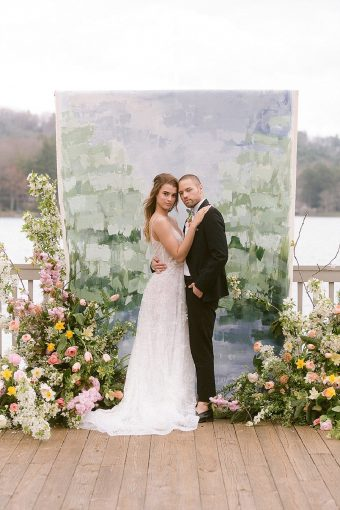 bridal couple with painted wedding ceremony backdrop with flowers