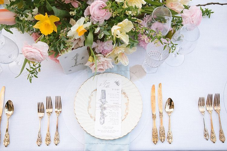 place setting with pink and yellow spring flowers, vintage tableware and gold cutlery, handpainted menu