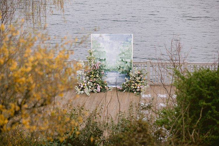 painting inspired wedding ceremony backdrop with wild and abundant pastel spring flowers