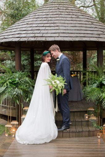 outdoor wedding ceremony with greenery and bridal cape