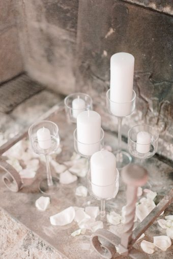 white candles and rose petals against french stone building