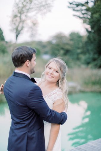 bride and groom at romantic outdoor brittany wedding ceremony with pool