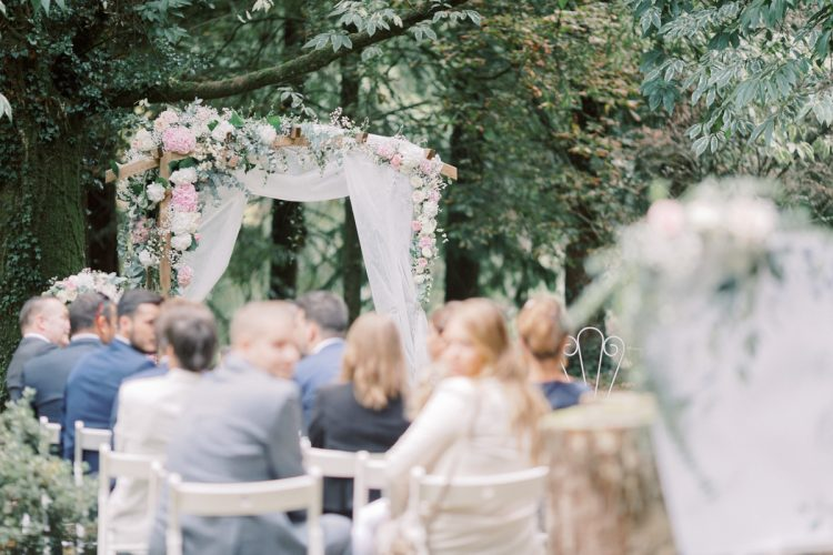 guests at romantic outdoor brittany wedding ceremony with blush floral arch