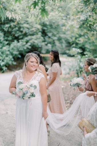 bride with blush wedding bouquet and long veil