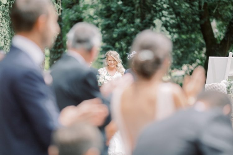 guests looking at bride at romantic outdoor brittany wedding ceremony