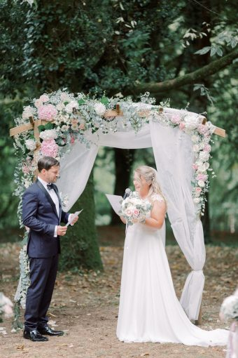 outdoor ceremony arch with white fabric and blush hydrangeas and foliage