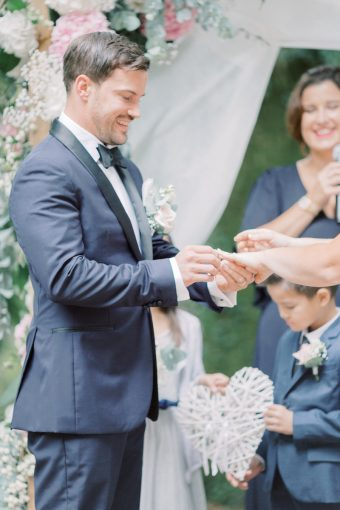 exchanging rings at romantic outdoor brittany wedding ceremony
