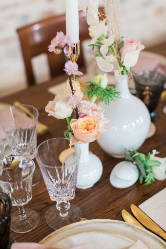 vases of peach and blush wedding flowers on a rustic table